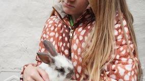 Barnflicka som rymmer en kanin på henne händer arkivfilmer