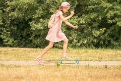 Barnflicka som skateboarding i en parkera Royaltyfri Fotografi