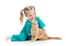 Barnflicka som spelar doktorn med katten Arkivbild