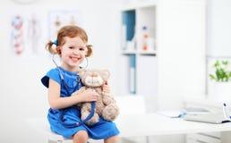 Barnflicka som spelar doktorn med nallebjörnen Arkivbilder