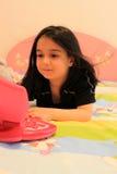 Barnflicka som spelar med bärbara datorn Fotografering för Bildbyråer