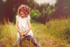 Barnflicka som spelar med sidor i utforskning för sommarskognatur med ungar royaltyfria bilder