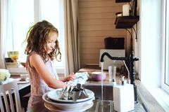 Barnflickahjälp fostrar hemma och tvättar disk i kök Tillfällig livsstil i verklig inre Arkivbilder