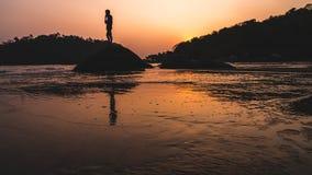 Barnflickajämvikt på tråden på goastranden på solnedgången royaltyfri fotografi
