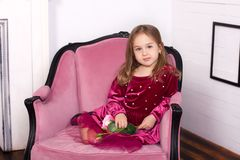 Barnflickan är härlig, gullig, gladlynt och lycklig på en rosa fåtölj i en trendig lyxig klänning lyckligt barndombegrepp royaltyfri foto