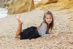 Barnflickan bär den avrivna klänningen på stranden Arkivfoton