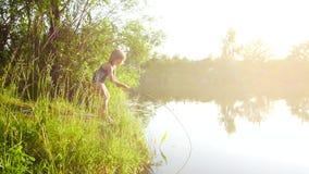 Barnflickan fångar fisken i floden med en pinne Utbrett ljus för härlig solnedgång stock video