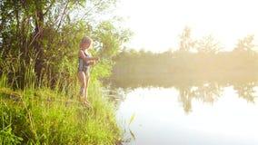 Barnflickan fångar fisken i floden med en pinne Utbrett ljus för härlig solnedgång lager videofilmer