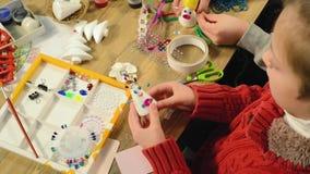 Barnflickan gör garnering för ferier Hantverk och leksaker, julträd och annat Målningvattenfärger Top beskådar artistically stock video