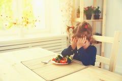 Barnflickan gillar inte och önskar inte för att äta grönsaker Royaltyfri Fotografi