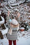 Barnflickan hänger fågelförlagemataren på trädet i snöig trädgård för vinter Royaltyfria Bilder