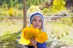 Barnflickan i nedgång för guling för höstpoplarskog lämnar in för att räcka Arkivfoto