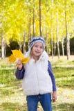Barnflickan i nedgång för guling för höstpoplarskog lämnar in för att räcka Arkivbild