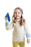 Barnflickan klädde som piloten som spelar med isolator för det pappers- flygplanet arkivfoton
