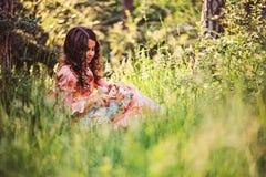 Barnflickan klädde som sagaprinsessan som spelar med dockan i sommarskog Fotografering för Bildbyråer