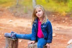 Barnflickan kopplade av på en treestam Arkivfoton