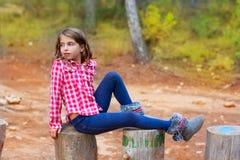 Barnflickan kopplade av på en treestam Arkivbilder