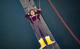 Barnflickan ligger på träbron och leenden på bakgrund av riv royaltyfri bild