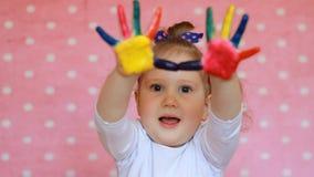 Barnflickan med gömma i handflatan i mångfärgad målarfärg Lyckligt behandla som ett barn med målade smutsiga händer stock video