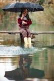 Barnflickan med paraplyet sitter på träbron och laughes i rommar royaltyfri foto