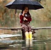 Barnflickan med paraplyet sitter på träbron och laughes i rommar arkivbilder