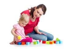Barnflickan och hennes mamma spelar med byggnadskvarter Arkivbild