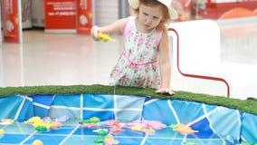 Barnflickan på lekplatsen spelar en lek av fiske och försök för att finna jämvikt arkivfilmer