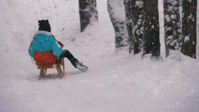 Barnflickan på träsläden går ner från en snöig kulle sörjer in Forest Slow Motion stock video