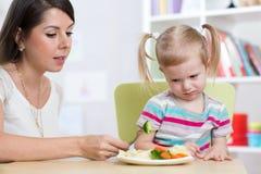 Barnflickan ser med avsmak på sunda grönsaker Modern övertygar hennes dotter för att äta mat royaltyfri foto