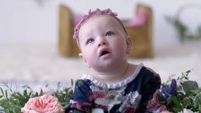 Barnflickan ser upp med den öppna munnen på fotofors i studio med den dekorativa blommacloseupen lager videofilmer