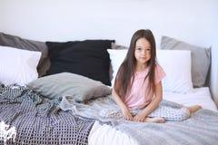 Barnflickan sitter på sängen i pyjamas arkivbild
