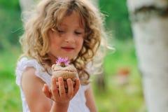 Barnflickan som spelar med den salta degkakan, dekorerade med blomman Arkivbild