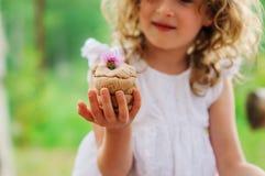 Barnflickan som spelar med den salta degkakan, dekorerade med blomman Royaltyfri Bild