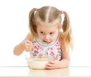 Barnflickan som äter havreflingor med, mjölkar Arkivbild