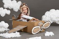 Barnflickan spelar i ett flygplan som göras av kartongen och drömmar av att bli en pilot, moln av bomull på en grå backgrou royaltyfri bild