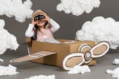 Barnflickan spelar i ett flygplan som göras av kartongen och drömmar av att bli en pilot, moln av bomull på en grå backgrou royaltyfria foton