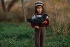 Barnflickan står med korpsvart i hennes händer på bakgrund av gräsplan royaltyfri fotografi