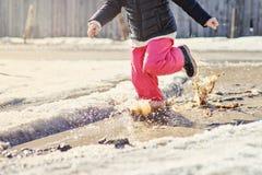 Barnflickaspring i vårpöl med stor färgstänk Arkivfoto