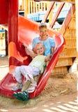 Barnflyttning ut att glida i lekplats. Arkivfoton