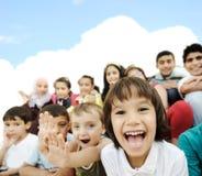 barnfolkmassa som tillsammans sitter Arkivbild