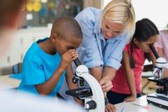 Barnforskare som ser till och med mikroskopet fotografering för bildbyråer