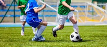 Barnfotbollspelare som kör med bollen Ungar i blått- och gräsplanskjortor Royaltyfri Bild