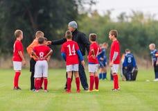 Barnfotbollspelare som spelar fotboll, och lagledare som utbildar th Royaltyfri Bild