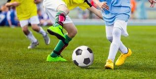 Barnfotbollsspelare som jagar bollen Ungesportduell arkivfoto