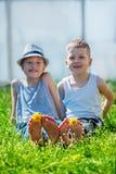 Barnfoten med maskrosen blommar att ligga på grönt gräs i s Arkivbilder