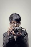 Barnfotograf som rymmer en kamera inomhus arkivfoton