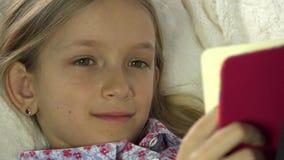 Barnframsidaläsebok på soffan, flicka, ungestående som studerar i säng, lagledare 4K stock video