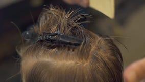 Barnfrisör som kammar och fixar hår av pysen för ungefrisyr i frisyrsalong Barnfrisyrslut stock video