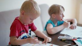 Barnfritidsaktivitet hemma: pojken och flickan drar på papper arkivfilmer
