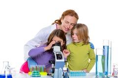 Barngirlas och lärarekvinnan på skolar laboratoriumet Arkivbild